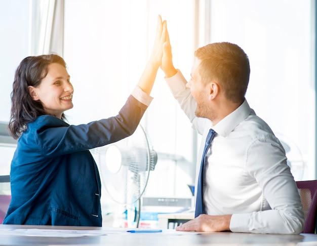 Onderneemster twee en zakenman die hallo-vijf in het bureau geven