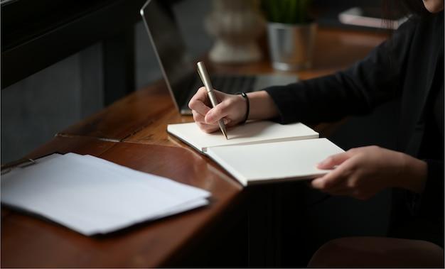 Onderneemsterhand die op notitieboekje schrijven