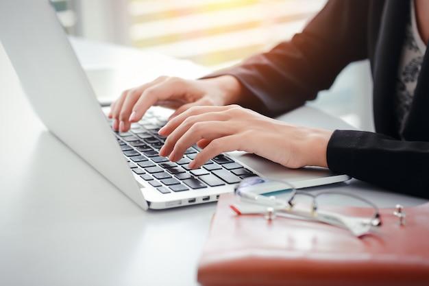 Onderneemsterhanden met glazen die computer met behulp van
