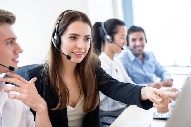 Onderneemstertelemarketing personeel die met medewerker in call centrekantoor werken