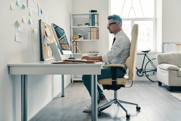 Ondernemen is zijn leven. doordachte jonge man in overhemd en stropdas die met de computer werkt terwijl hij op kantoor zit