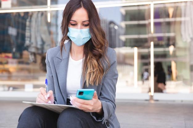 Ondernemende vrouw schrijft in haar notitieboekje terwijl ze naar haar smartphone kijkt. ze zit op straat en draagt een medisch masker.