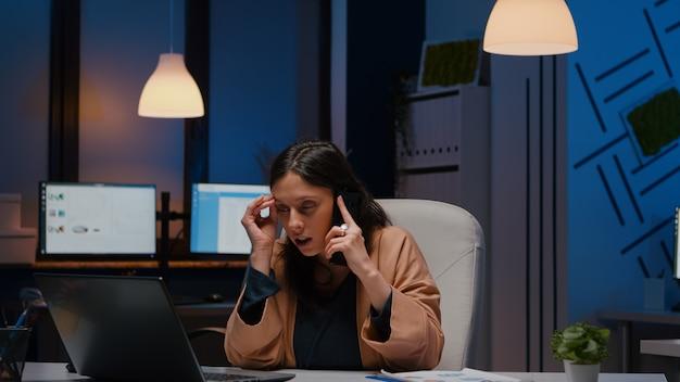 Ondernemer benadrukte vrouw die marketingstrategie analyseert op laptop in gesprek met bedrijfsmanager