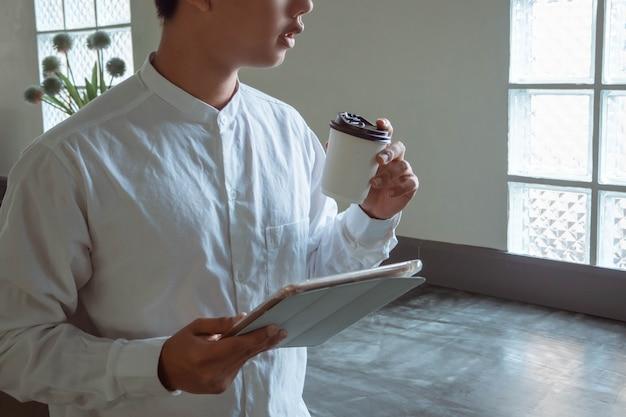 Ondernemer concept een slimme zakenman die met zijn apparaten aan zijn werk werkt terwijl hij geniet van een kopje drank.