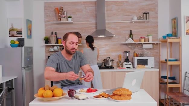 Ondernemer die aan laptop in keuken werkt en koffie drinkt terwijl vrouw ontbijt kookt. freelancer werkt online via internet met behulp van moderne digitale technologie