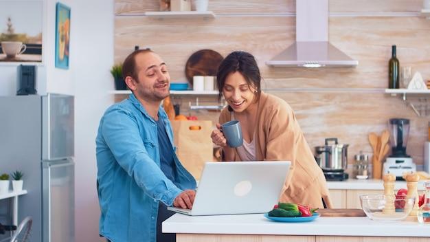 Ondernemer die aan laptop in keuken werkt en vrouw die een kop koffie houdt die zijn werk bekijkt. man en vrouw koken recept eten. gelukkig gezond samen levensstijl. familie op zoek naar online maaltijd