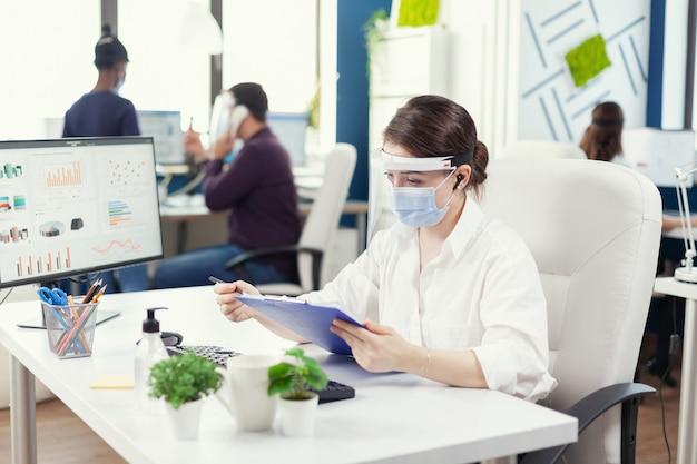 Ondernemer die gezichtsmasker draagt tegen covid19 met behulp van draadloze hoofdtelefoons voor bellen op afstand. werknemers met vizieren die in de werkruimte van het bedrijf werken en de sociale afstand respecteren, analyseren van gegevens en gra