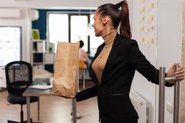 Ondernemer die glas opent op bedrijfskantoor met afhaalmaaltijden voor lunchmaaltijd. zakelijke zakenvrouw met papieren zak met heerlijke fastfood afhaalmaaltijden geleverd door een man.