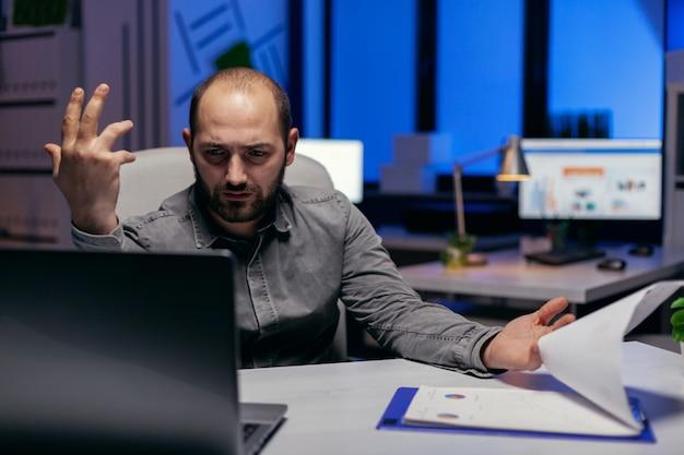 Ondernemer die het project probeert te begrijpen dat aan zijn bureau zit in een leeg kantoor. verwarde zakenman terwijl hij overwerkt om een groot project voor het bedrijf af te ronden.