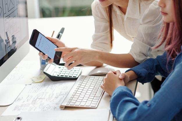 Ondernemer die kalender op smartphonescherm toont aan jonge ui-ontwerper die werkt aan de interface van nieuwe mobiele applicatie en deadline stelt
