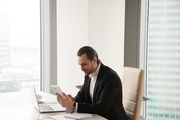 Ondernemer die tablet gebruiken terwijl het zitten bij bureau