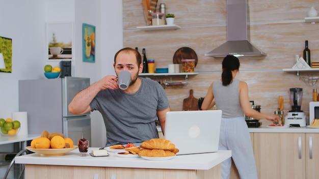 Ondernemer die vanuit huis werkt terwijl hij ontbijt eet in de keuken, pyjama draagt en geniet van geroosterd brood met boter. freelancer die online werkt via internet met behulp van moderne digitale technologie