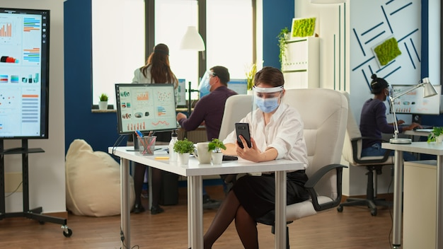Ondernemer die vizier draagt tegen coronavirus met behulp van telefoon met draadloze hoofdtelefoon voor videogesprekken met een team op afstand dat in een nieuw normaal kantoor zit. collega's die werken met respect voor sociale afstand