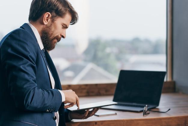 Ondernemer in de buurt van het raam met een laptop communicatie