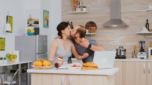 Ondernemer laat op het werk tijdens het ontbijt met vrouw in de keuken. gestresste man laat haastig nerveus rennend snel naar ontmoeting, haast om te werken, te laat voor afspraak. zoenen vrouw goodbuy en rennen naar