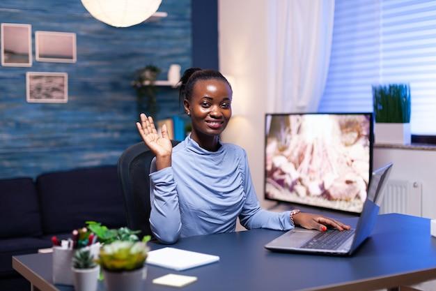 Ondernemer met donkere huidskleur zwaait tijdens gesprek tijdens videogesprek op afstand. afrikaanse zakenvrouw zegt hallo zwarte freelancer die werkt met een team op afstand dat virtueel online vergadert