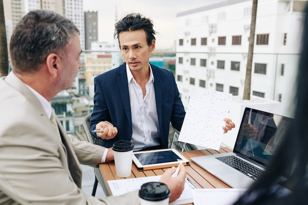 Ondernemer toont grafiek aan zijn collega's wanneer ze een vergadering op het dak hebben