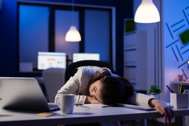 Ondernemer werkt overuren aan marketingproject, valt in slaap op het bureau terwijl hij naar financiële documenten kijkt en probeert de deadline te respecteren