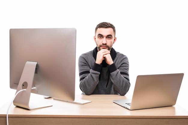 Ondernemer zit aan de tafel met laptop en personal computer en kijkt naar camera geïsoleerd op wit