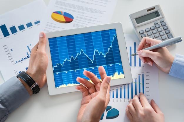 Ondernemers analyseren grafiek met digitale tablet