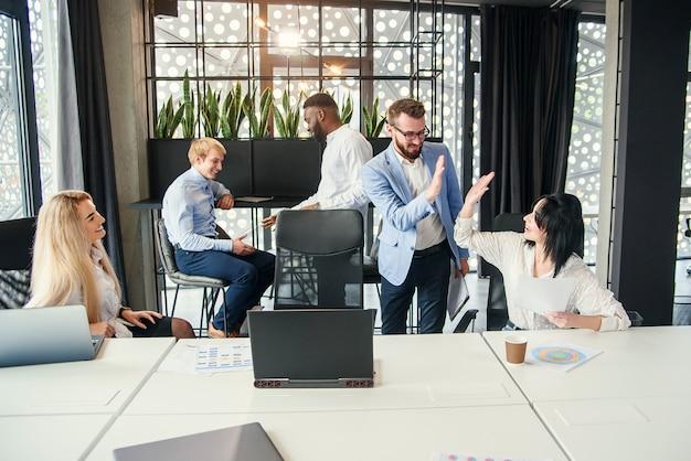 Ondernemers begroeten hun kantoorcollega's met high five voor aanvang van de werkzaamheden in het kader van een gezamenlijk zakelijk project in het moderne kantoor.