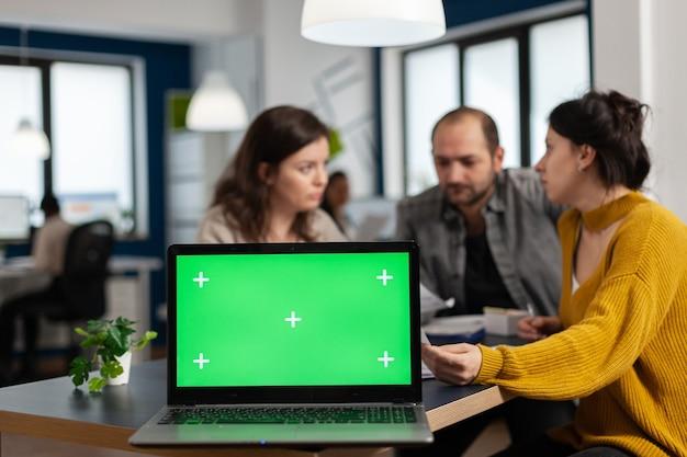 Ondernemers die jaarlijkse financiële rapporten analyseren die aan een bureau achter een laptop zitten met een chroma key-display met groen scherm, mock-up desktop