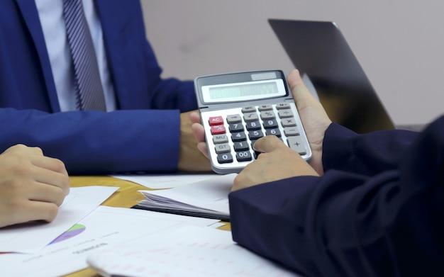 Ondernemers die op calculators drukken om baangegevens voor bedrijfs- en marketingplannen te analyseren