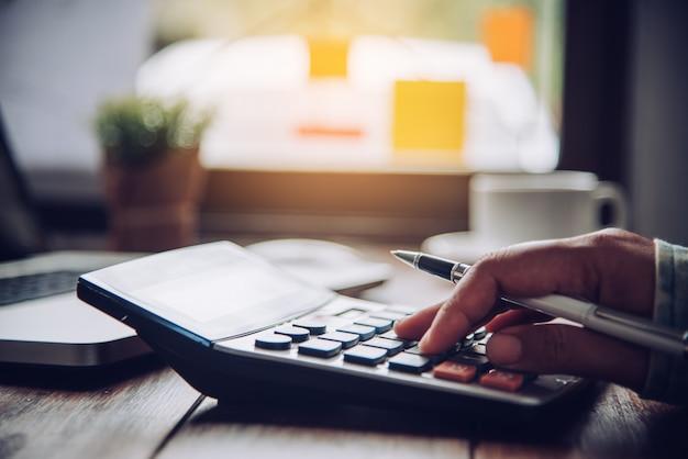 Ondernemers gebruiken een calculator om het inkomen van het bedrijf te berekenen.