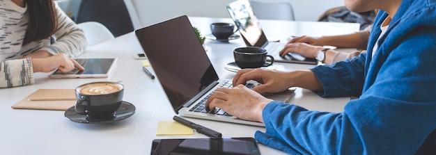 Ondernemers gebruiken en werken op laptopcomputer en tablet-pc op tafel in kantoor