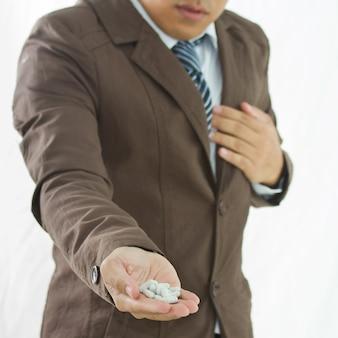 Ondernemers hebben drugs bij de hand, bijgesneden afbeelding van zakenman met een pijn op de borst