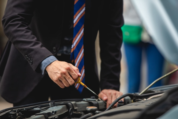 Ondernemers helpen zakenvrouwen bij het controleren en repareren van kapotte auto's