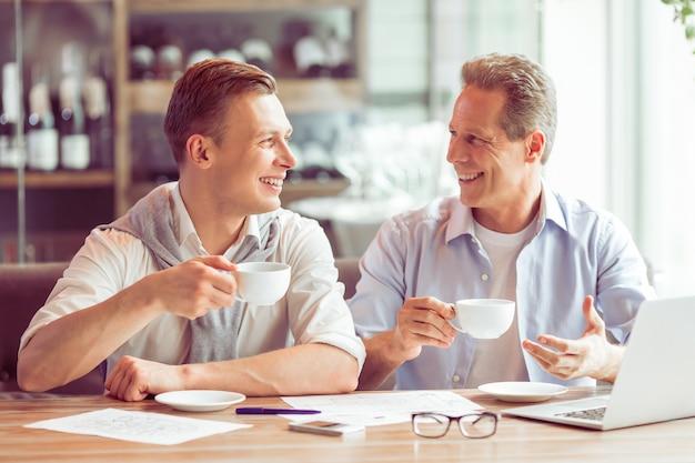 Ondernemers in vrijetijdskleding drinken koffie.