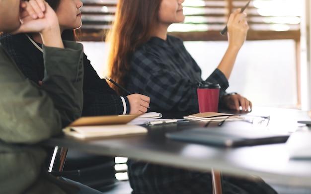 Ondernemers kijken en bespreken ideeën over een bord in kantoor