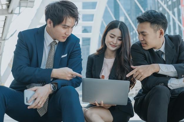 Ondernemers kijken naar laptop en discussie over project
