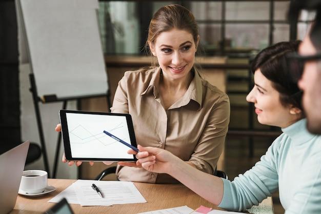 Ondernemers met een bijeenkomst binnenshuis en met behulp van tablet