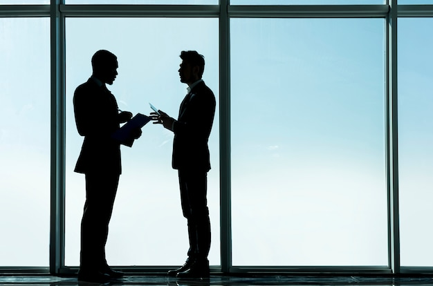 Ondernemers staan op kantoor met panoramische ramen.