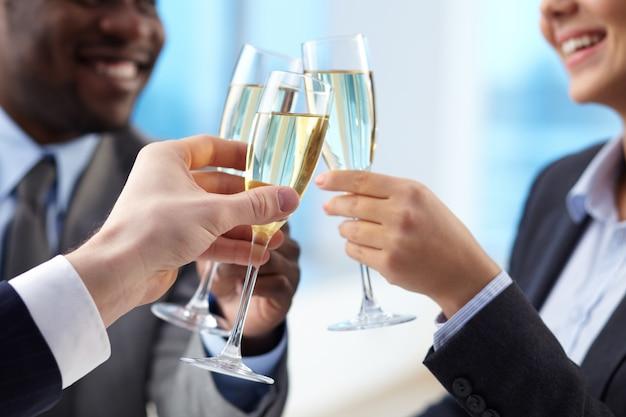 Ondernemers vieren van de overeenkomst met champagne