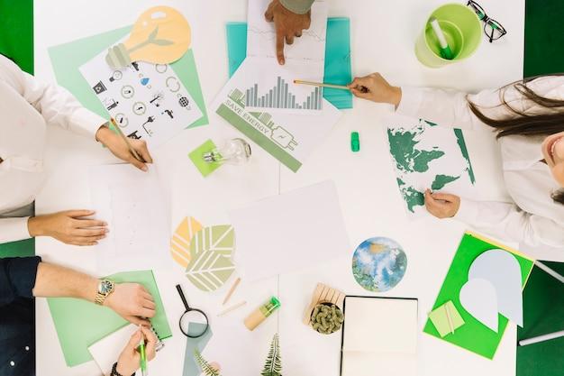 Ondernemers werken aan grafiek met verschillende natuurlijke hulpbronnen pictogram op bureau