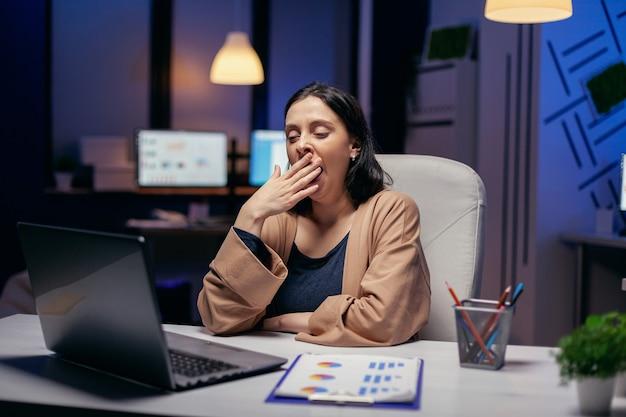 Ondernemersdame gaapt aan de deadline in een donker kantoor en kijkt naar het scherm van de laptop. slimme vrouw zit op haar werkplek in de loop van de late nachturen en doet haar werk.