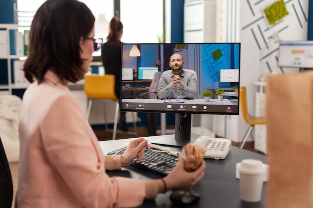 Ondernemersvrouw die aan het bureau in het kantoor van het bedrijf zit en een broodje eet tijdens een online videogesprekconferentie over financiële strategie. afhaalbestelling eten bezorgen op zakelijke werkplek