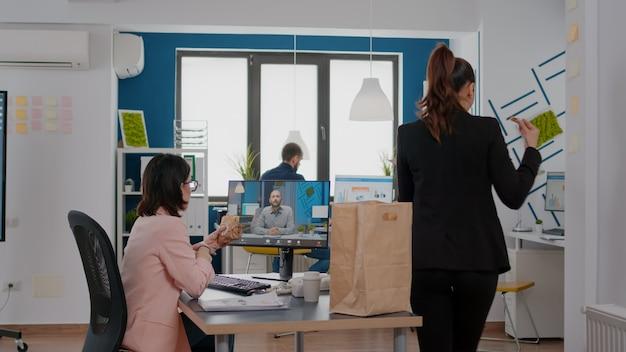 Ondernemersvrouw die aan het bureau zit in het kantoor van het bedrijf en een broodje eet tijdens een online videogesprekconferentie