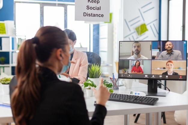 Ondernemersvrouw op externe videoconferentiediscussie op nieuwe normale werkplek tijdens wereldwijde pandemie met covid19-griep, met gezichtsmasker en sociale afstand. internet web videogesprek online chatten