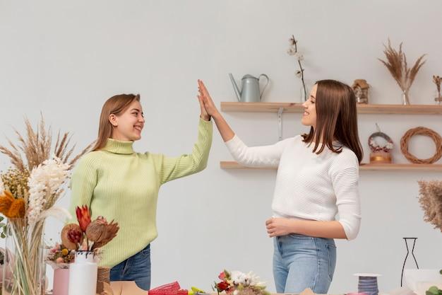 Ondernemersvrouwen in hun kleine bedrijf high five