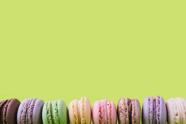 Onderrand gemaakt met kleurrijke bitterkoekjes op groene achtergrond