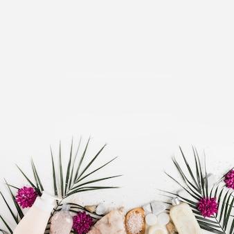 Onderrand met bloem; verlaat; spa stenen; lichaam boenen en zout op witte achtergrond