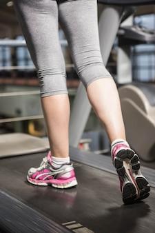 Onderste gedeelte van een vrouw op een loopband in de sportschool