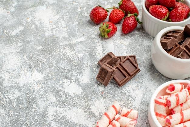 Onderste halve schaal met aardbeienchocolade snoepjes en wat aardbeienchocolade snoepjes aan de rechterkant van de grijs-witte mozaïekachtergrond
