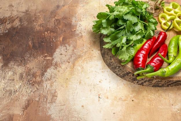 Onderste helft bekijk verschillende groenten koriander hete pepers paprika in stukjes gesneden op ronde boom houten bord op amber achtergrond vrije ruimte