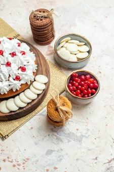 Onderste helft cake met witte banketbakkersroom op een houten bord op krantenbessen en witte chocolade in kommen, koekjes vastgebonden met touw op lichtgrijs oppervlak