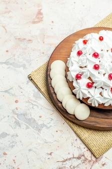 Onderste helft cake met witte banketbakkersroom op houten bord op krant op lichtgrijs oppervlak